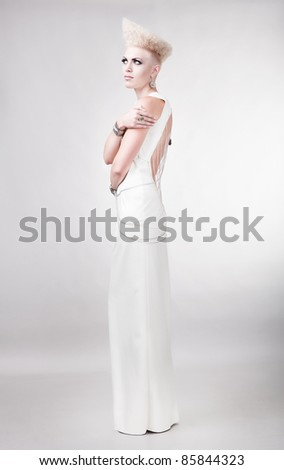 blond magnificent woman in white dress with creative hairstyle