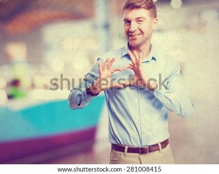 blond man heart sign - stock photo