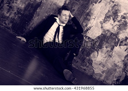 Blond man in depression sitting on the floor. Dressed in a formal classic suit. Antique colour graded. - stock photo