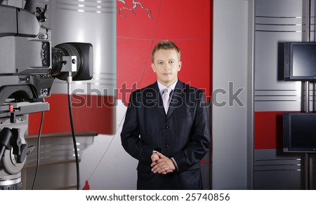 blond middle age news presenter in studio in front of the camera with braking news reports - stock photo