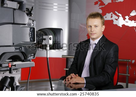 blond middle age news presenter in studio in front of the video camera - stock photo