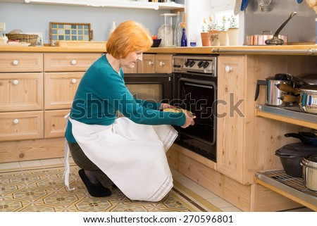 Blond Middle Age Woman With Apron Putting a Cake for Snacks in an Oven at the Home Kitchen. - stock photo
