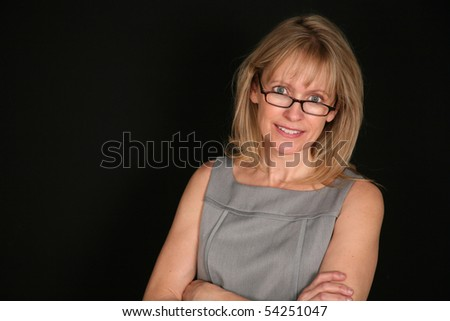 blond middle aged woman on black background smiling
