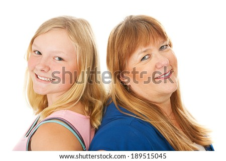 Blond mother and beautiful teenage daughter standing back to back.  Isolated on white. - stock photo