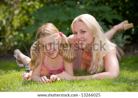 Blond mother with her daughter lying in the grass on a summer day - stock photo