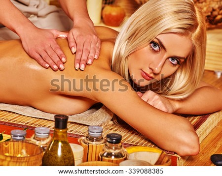 Blond naked woman getting massage in tropical spa. - stock photo