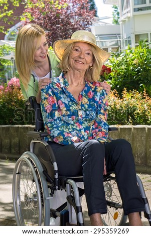 Blond Nurse Standing Behind Senior Woman in Wheelchair Wearing Sun Hat in front of Retirement Building, Enjoying the Day. - stock photo