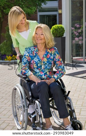 Blond Nurse Standing Behind Senior Woman in Wheelchair with Hand on Shoulder Outdoors in front of Retirement Home on Sunny Day. - stock photo