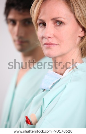 Blond nurse stood with male colleague - stock photo