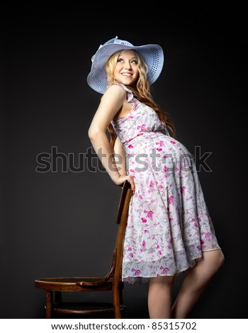 Blond pregnant woman portrait in straw hat - stock photo