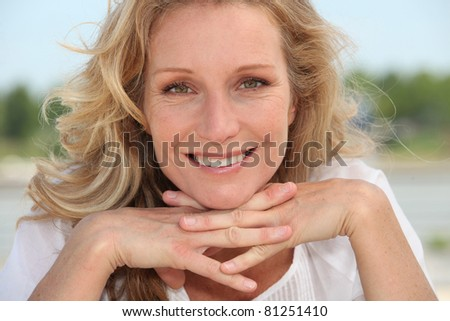 Blond resting head on hands - stock photo