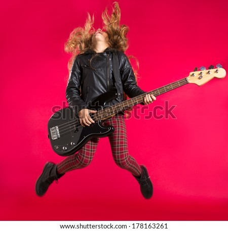 Blond Rock and roll girl jumping playing bass guitar on red background - stock photo