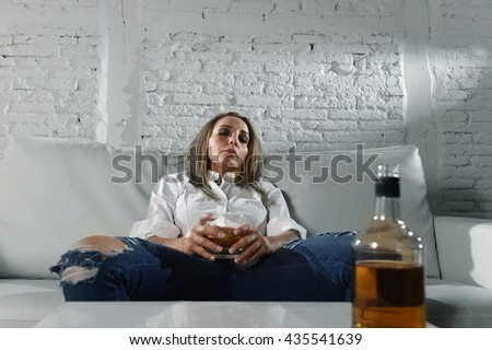 blond sad and wasted alcoholic drunk woman sitting at home sofa couch drinking scotch whiskey holding glass depressed lonely and suffering hangover in alcoholism and alcohol abuse concept - stock photo