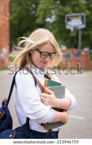 Blond school girl with nerd glasses. Selective focus. - stock photo
