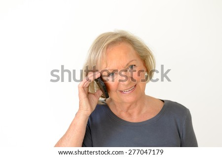 Blond senior woman with a friendly facial expression having a conversation on mobile phone, portrait with copy space on gray - stock photo