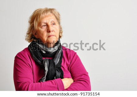 Blond senior woman with crossed arms deep in her thoughts over light grey background. - stock photo