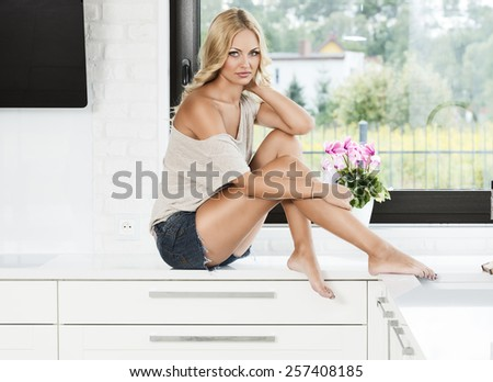 blond sexy woman in her white kitchen , sitting near the window and posing at the camera - stock photo