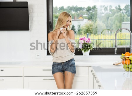 blond sexy woman in t-shirt and short , with a cup of hot coffee , looking out from a window - - stock photo