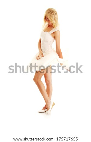 Blond sexy woman in white skirt blowed by wind, isolated on white background - stock photo