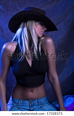 blond sexy woman, studio dark background, blue spot light - stock photo
