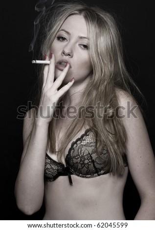 blond sexy wome in bra smoking - stock photo