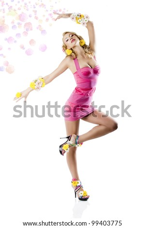 Blond sexy young woman wearing a pink summer dress and lot of color flowers on arm and shoes, she is in front of the camera and looks in to the lens in a ballet position with left leg and left arm - stock photo