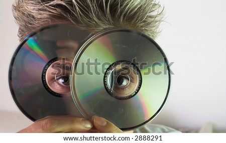 Blond short hair woman woman with white Tshirt looking through a CD hole - stock photo