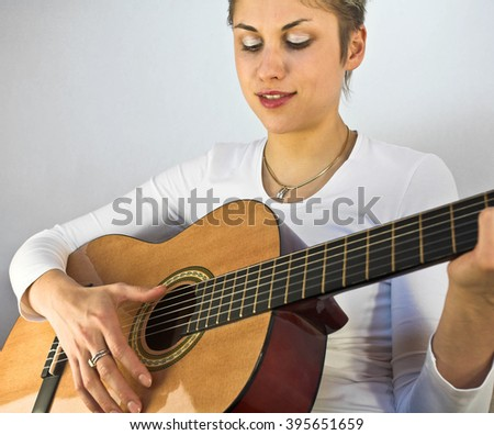Blond short hair woman woman with white Tshirt playing acoustic guitar - stock photo
