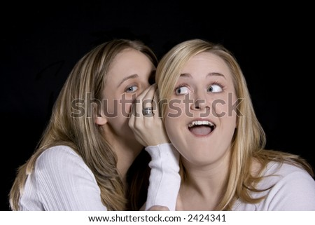 blond sisters whispering secrets - stock photo