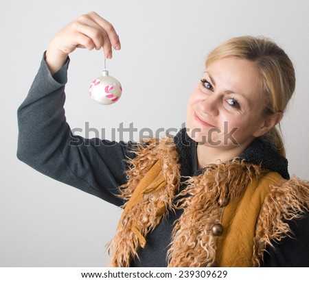 Blond smiley girl holding handmade glass xmas ball on a grey background - stock photo