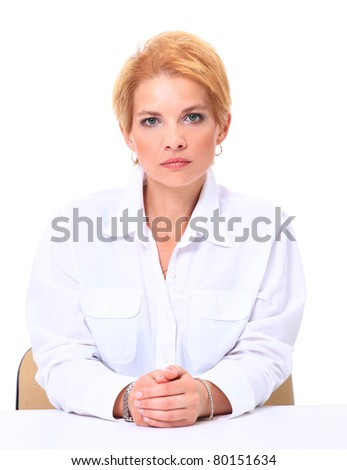 Blond smiling businesswoman sitting at her desk isolated on white background