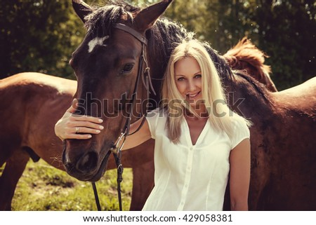Blond smiling female posing with brown horses in a field.