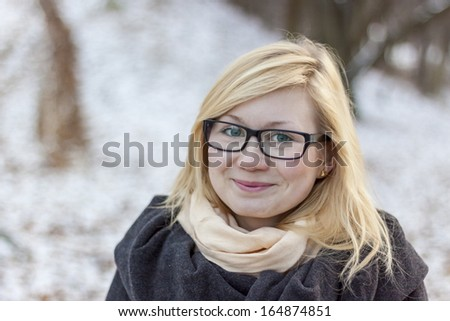 Blond smiling girl in park - winter time. - stock photo