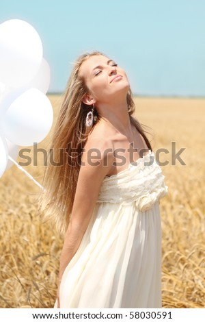 Blond smiling girl with white balloons in the field