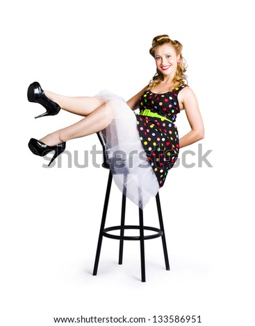 Blond smiling pinup woman in colorful polka dot dress sitting on bar stool isolated on white background - stock photo