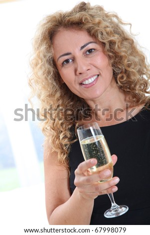 Blond smiling woman holding glass of champagne