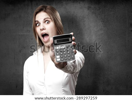 blond surprised woman with calculator - stock photo