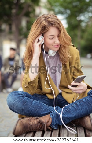 Blond Teen Girl Sitting on the Wooden bench with Legs Crossed, Listening Music From her Mobile Phone Using Headphone. - stock photo