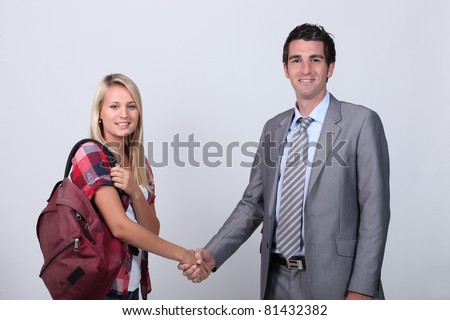Blond teenage girl shaking teacher's hand - stock photo
