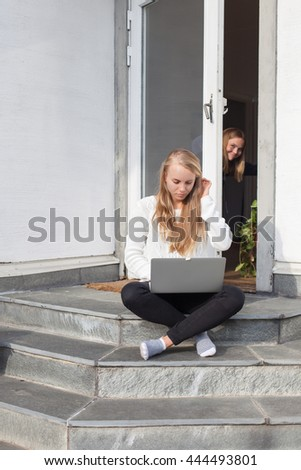 Blond, teenage, Swedish girl sitting on stairs outside, writing on her computer, fixing her hair whilst sister is looking out behind glass door.  - stock photo