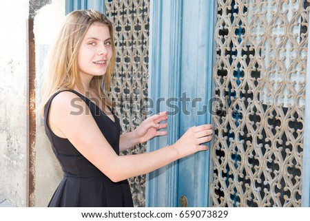 blond teenager girl in front of blue door fashion