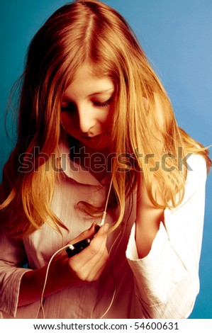 blond teenager girl listening music on her mp3 player - stock photo