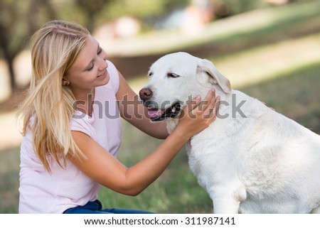 blond teenager with fourteen years old  labrador dog in the park, selective focus