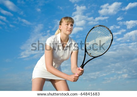 Blond tennis player with tennis racket on background of the sky - stock photo