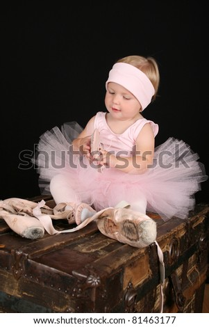 Blond toddler wearing a tutu holding Ballet shoes - stock photo