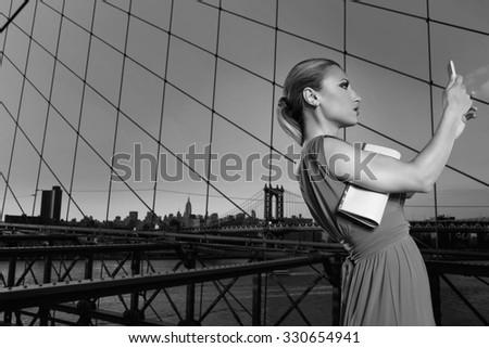Blond tourist girl selfie photo in Brooklyn Bridge New York at night sunset Photomount - stock photo