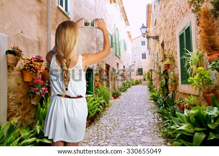 Blond tourist girl taking photos of Mallorca Valldemossa village street photomount - stock photo