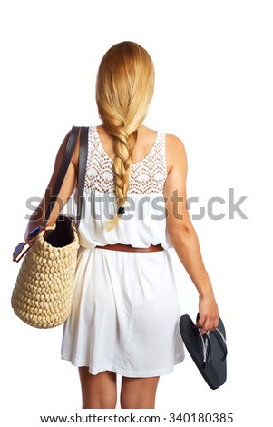 Blond tourist girl with flip flop shoes white summer dress and basket bag going beach rear view