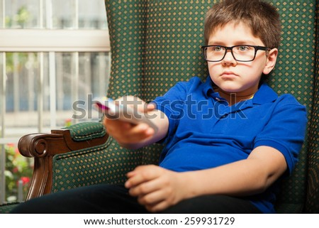 Blond tween relaxing at home and surfing channels on TV with a remote - stock photo