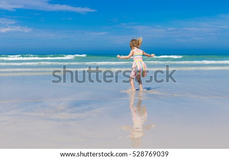 blond vaulting girl in multicolored dress vaulting on beach resort happily spending her holidays in tropical country